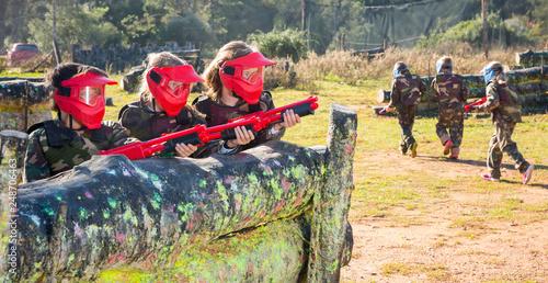 Fototapeta Opposing teams of happy kids shooting paintball