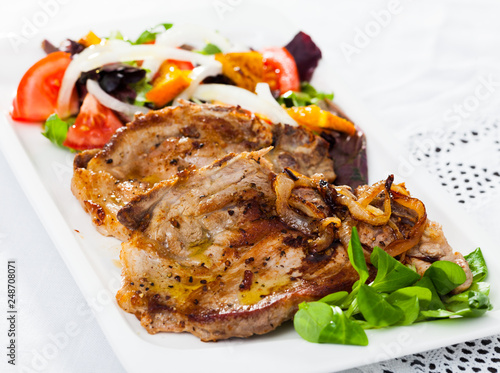 Fried pork meat chops with salad of fried orange and vegetables
