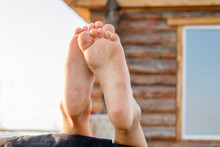 Barefoot Baby Feet On The Background Of A Rustic Wooden House