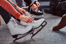 Young Couple Preparing To A Skating. Close-up Photo Of Their Hands Tying Shoelaces Of Ice Hockey Skates In A Locker Room