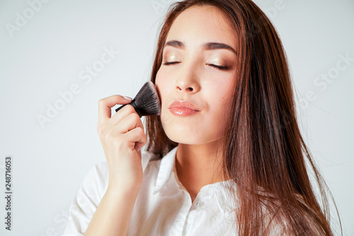 Fotografia Make up brush kabuki in hand of smiling asian young woman with dark long hair on