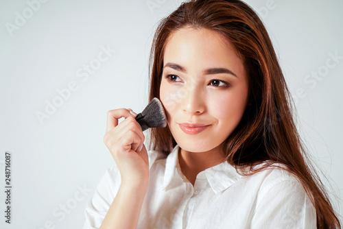 Make up brush kabuki in hand of smiling asian young woman with dark long hair on Fototapeta