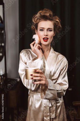Photo  Young attractive woman with wavy hairstyle and red lips in silk robe applying po