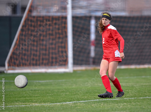 Photo  Young high school girl competing in a soccer match