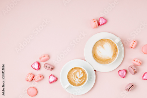 Coffee cups with candys and macaroons on pale pink background. Flat lay, top view