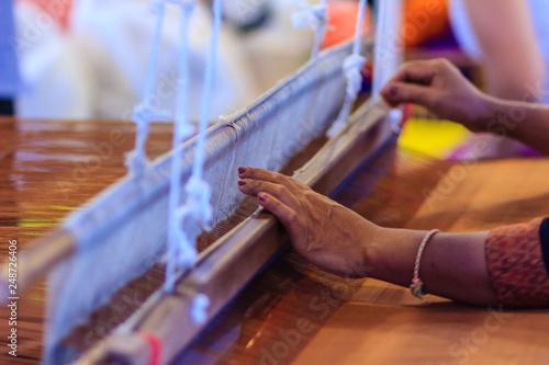 Fotografie, Obraz  Weaver using small loom or weaving machine for weaving fabric