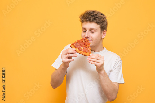 Fotografie, Obraz  Young man holds a piece of fresh pizza in his hands to smell a scent with his eyes closed, isolated on a yellow background