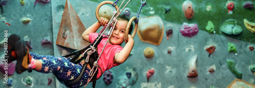 Little girl in sports clothes doing exercises on sports rings on rock wall indoor . The concept of a healthy lifestyle from a young age. Children sport.
