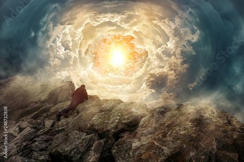 Obraz Mann auf einem Felsengipfel schaut in einen surrealen Wolkentunnel - fototapety do salonu
