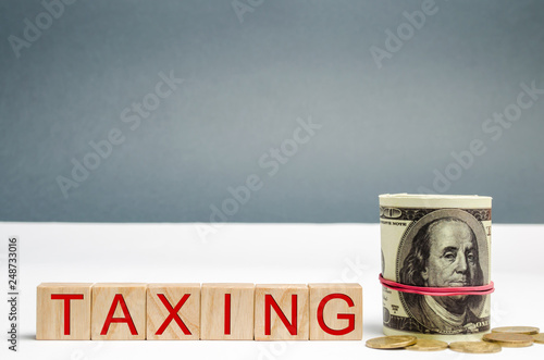 Photographie  Wooden blocks with the word Taxing and dollars