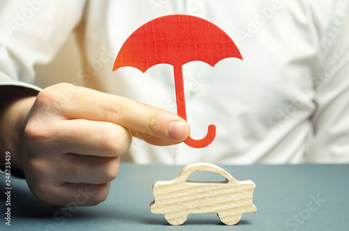 Fotografía  An insurance agent is holding a red umbrella over a miniature wooden car