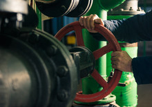 Man Holding Red Valves In Technical Room With Water Supply Pipes