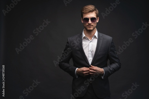 Fotomural  Stylish young man in suit and sunglasses