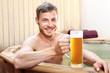 Piwne spa. Przystojny mężczyzna zażywa kąpieli w bali z woda termalną pijąc piwo kuflowe.