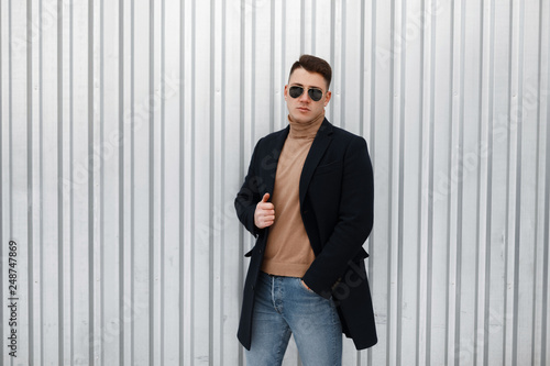f413a8c6d86 Elegant young hipster man in a knitted sweater in a stylish black coat in  sunglasses in trendy jeans with a stylish hairstyle stands near the metal  wall.