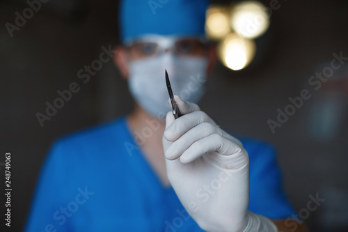 Foto Professional surgeon in blue uniform in a medical mask in sterile gloves holds a metal scalpel in his hand