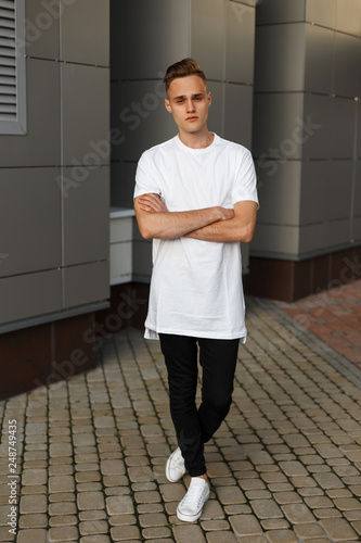 Attractive handsome young man in a white stylish T-shirt in