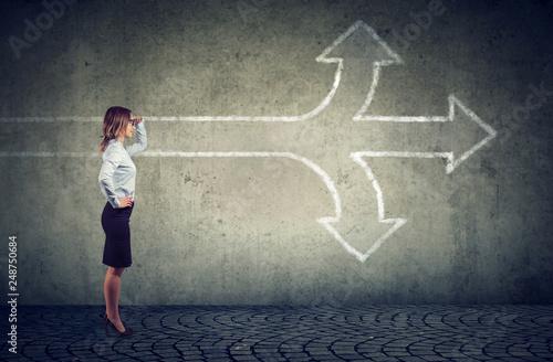 Fototapeta Confident businesswoman looking into the future at crossroads