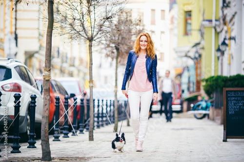 Fotografía  young redhaired Caucasian woman walking along European street with small Chihuahua breed dog of two colors on leash
