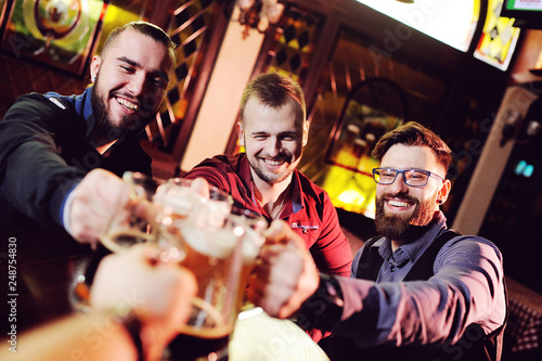 friends - young cute men drink beer in a bar, ringing glasses, smiling, laughing and talking Canvas Print