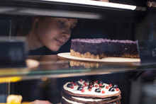 The Girl Waiter, Seller Putting Delicious Cake On The Store Showcase Of The Bakery House. Cake And People In Cafe Concept.