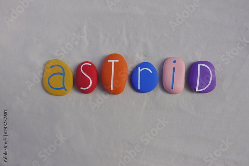 Photo  Astrid, feminine given name celebrated with multi colored stones over white sand