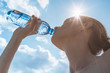 Leinwanddruck Bild - Female drinking bottle of water on a hot summer day.