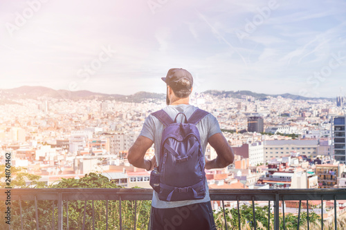 Foto auf AluDibond Weiß Traveler man looking on a big city, travel and active lifestyle concept.Bearded Tourist Man with backpack enjoy beautiful panoramic view of modern european city. Flare