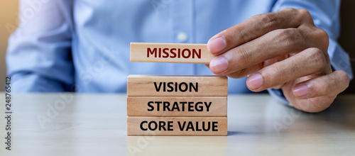 Businessman hand holding wooden building blocks with Businessman hand holding wooden building blocks with MISSION, VISION, CORE VALUE, STRATEGY concepts