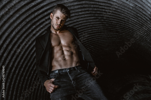 Fotografiet  Muscular young man with beard on dark tunnel urban background