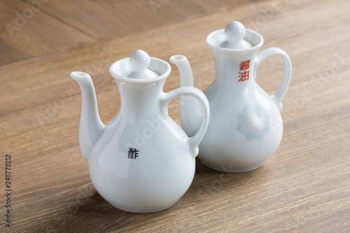 Fotografie, Obraz  中華の酢と醤油の入れ物(木目のテーブルバック)