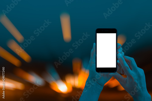 Fotografie, Obraz Hand holding smartphone with abstract bokeh of city night light background