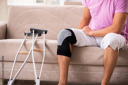 Carta da parati Young man with injured knee recovering at home