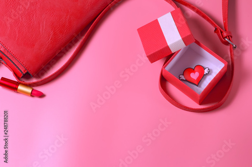 Photo Нeart in a red gift box, lipstick, women's bag on a pastel pink background