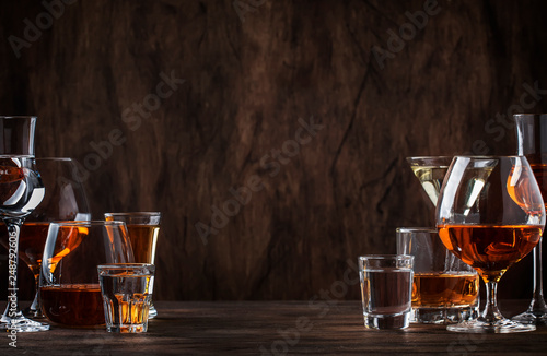 Foto auf Leinwand Alkohol Selection of hard strong alcoholic drinks in big glasses and small shot glass in assortent: vodka, cognac, tequila, brandy and whiskey, grappa, liqueur, vermouth, tincture, rum.