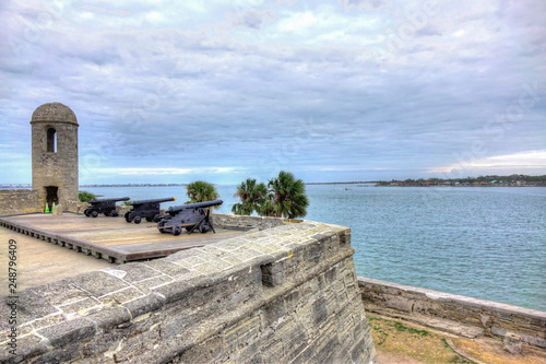 Three Spanish colonial cannons mounted on top of an old Spanish fort, overseeing the ocean, a cloudy sky and palm trees Wallpaper Mural