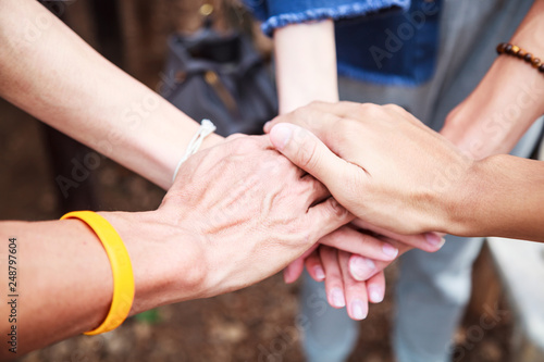 Fotografia  young men and women standing and stacking hands in a meeting on natural ground background at outdoor outing