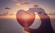 Love Is Happiness. Hand Holding Heart Against Sunset.