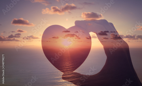 Obraz Love is happiness. Hand holding heart against sunset.  - fototapety do salonu