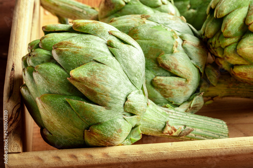 A closeup of a globe artichoke in a wooden crate Canvas Print