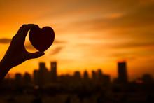 Hand Holding Heart Against City Sunset