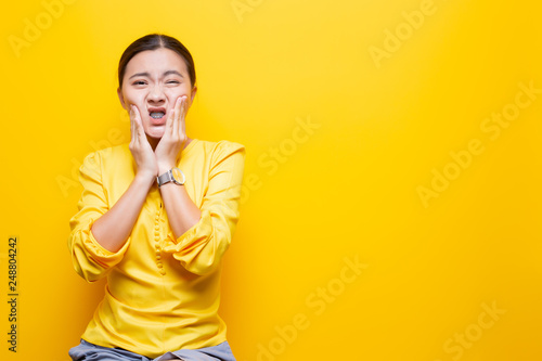 Fotografia  Woman has toothache isolated over yellow background