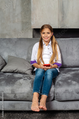 Pretty  barefoot  little girl sits on the sofa with red smartphone Canvas Print