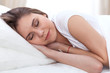 Beautiful young and happy woman sleeping while lying in bed comfortably and blissfully smiling
