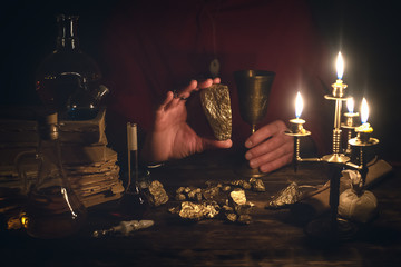 Alchemist is working at his magic table and producing a gold ore from a stones.