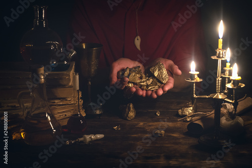 Photo  Alchemist is working at his magic table and producing a gold ore from a stones