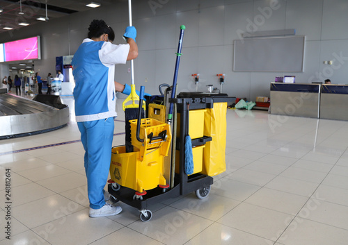 Fototapeta Closeup of woman cleaning worker doing her work with janitorial, cleaning equipment and tools