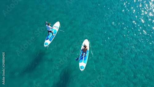 Fotografía Aerial drone bird's eye view of 2 men exercising sup board in turquoise tropical