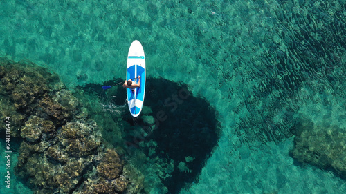 Photo  Aerial drone bird's eye view of 2 men exercising sup board in turquoise tropical