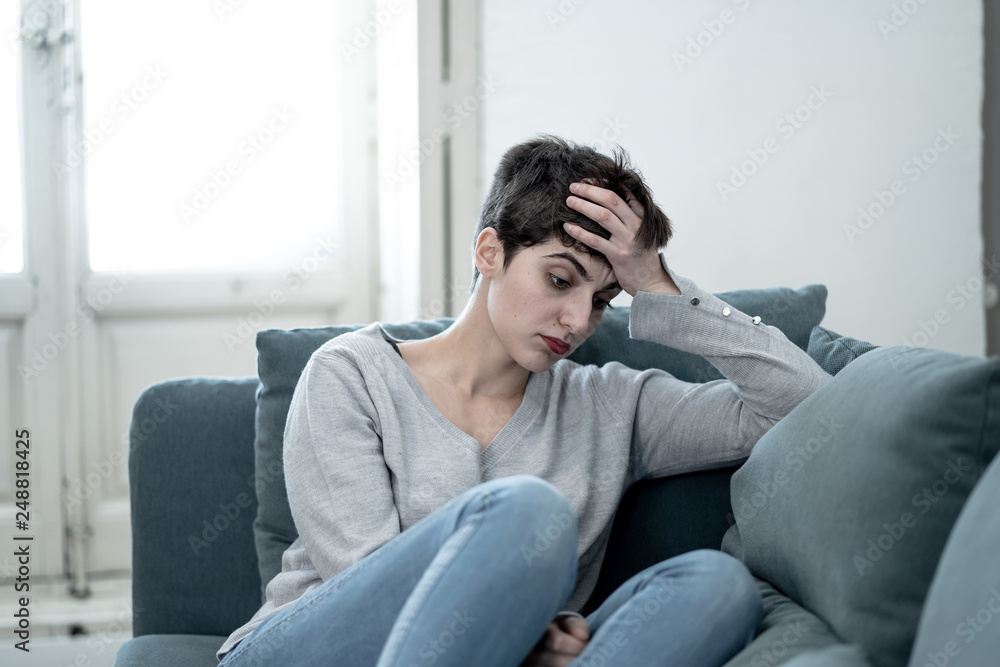 Fototapeta Attractive young woman looking down sad overwhelmed and lonely on the couch at home